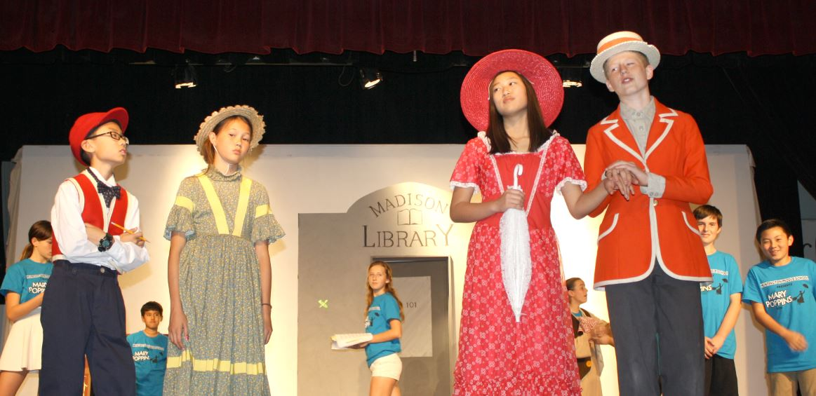 "OUTLOOK photo  Working on the park scene in Huntington Middle School's musical ""Mary Poppins"" are (from left) Stanley Wong as Michael Banks, Rae Bear as Jane Banks, Heein Kim as Mary Poppins and Logan Wing as Bert, with ensemble players behind. The show opens Feb. 25 and will be performed four times over that weekend."