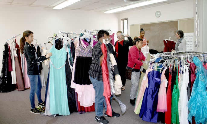 Photo by Merin McDonald / OUTLOOK Girls try on prom dresses donated by the Salvation Army. The program helps make the prom more affordable for students.