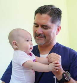 Photo courtesy John Chaides Dr. John Rodarte attends to one of many babies he sees during the Healing Hearts Across Borders' medical clinic in Tijuana, Mexico.