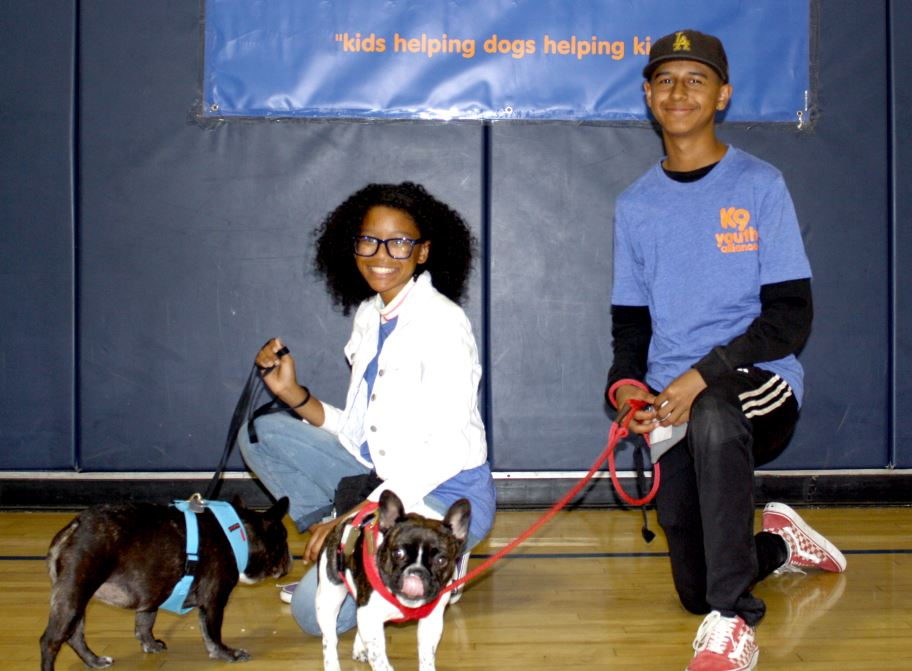 Photo by Camila Castellanos / OUTLOOK Boys & Girls Club members Zara, with dog Honey Badger, and Tony, with his special-needs dog Jodie Foster, both graduated recently from the K9 Youth Alliance dog-training program.