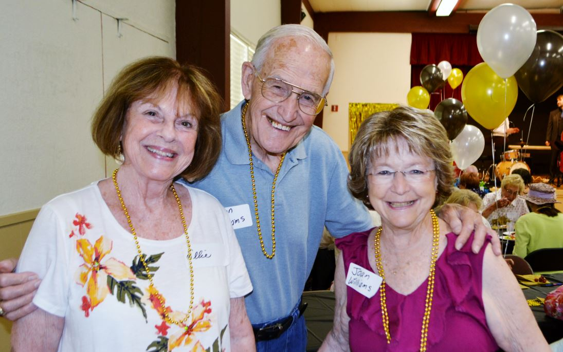 "Photo by Mary Emily Myers / OUTLOOK Ellie Wildermuth (left) and Joan Williams help Don Williams celebrate his 86th birthday at the""Swingin' Seniors"" event at the Community Center."