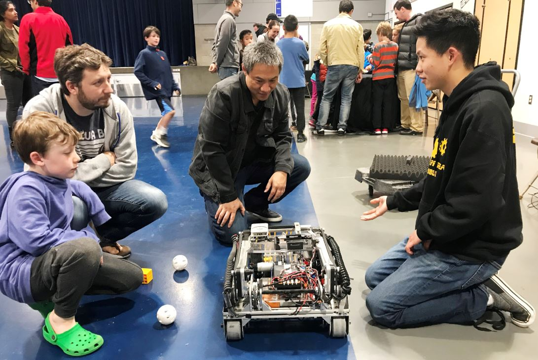 La Cañada Flintridge resident Brandon Cipes, his son Everett and STEM World's Joe Huprich listen to LCHS student Nathan Yun talk about his robot. Yun belongs to the Golden Gears robotics team.
