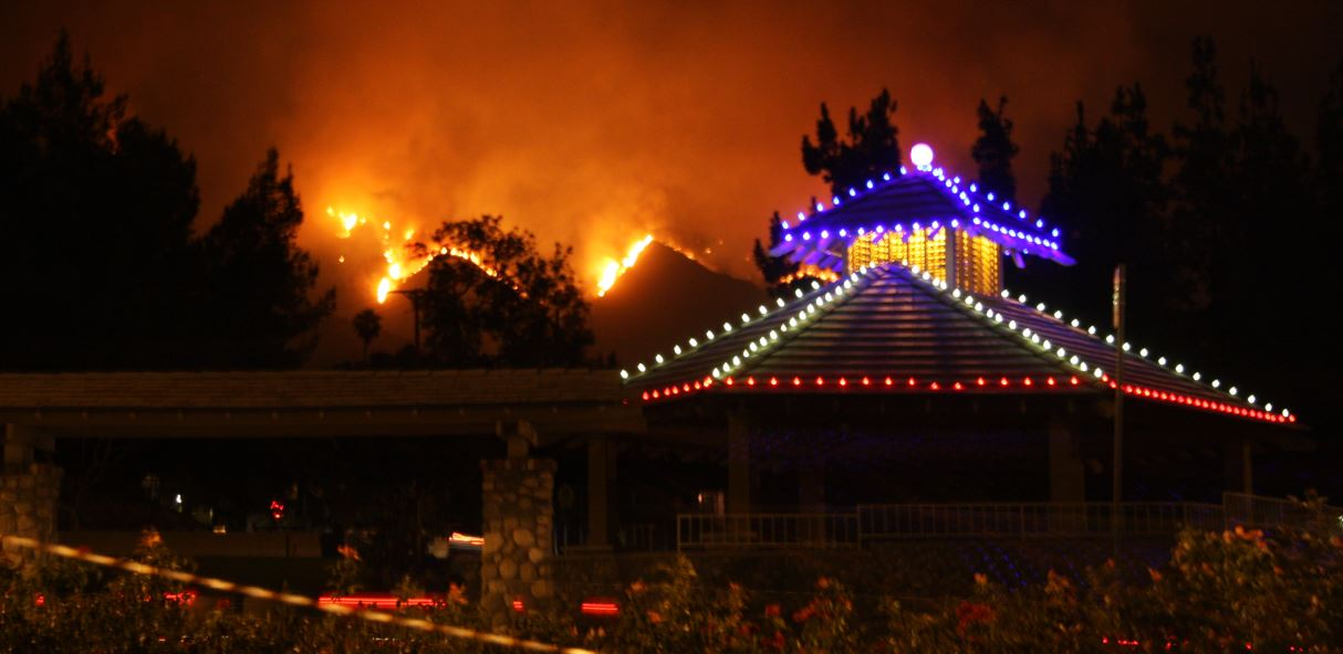 The lights of the Memorial Park gazebo contrast the devastation of the fire in the background.