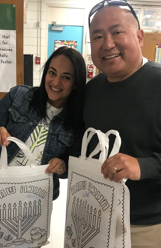 La Cañada Unified School District parent and education director for Temple Beth David Religious School Gal Kessler Rohs and Palm Crest Elementary School Principal Cory Pak display a Hanukkah kit created for kindergarten students on Wednesday.